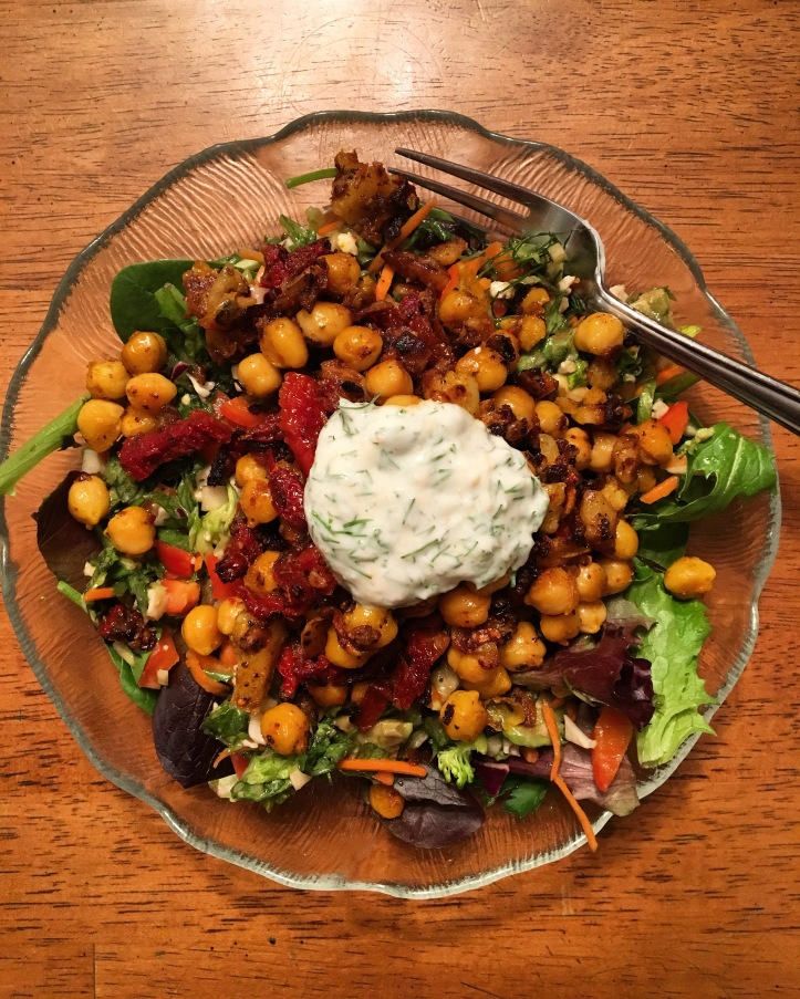 best healthy Garlicky Chickpeas with Sundried Tomatoes, Spinach, and Herbed Yogurt on a glass plate with a fork