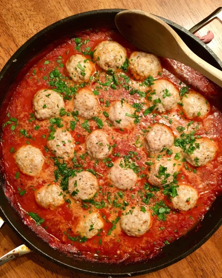 best healthy turkey meatballs with homemade tomato sauce in a skillet topped with fresh parsley