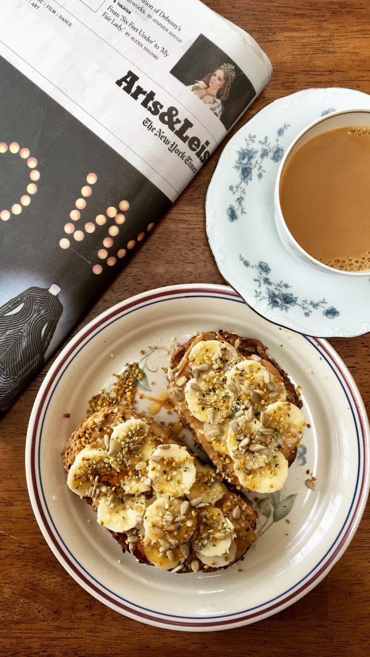 peanut butter and banana toast on a plate with a cup of coffee and the new york times