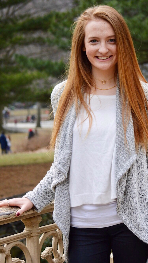Redheaded girl standing next to a fence with her hand on the fence, smiling and wearing a white shirt, gray cardigan, and black pants.