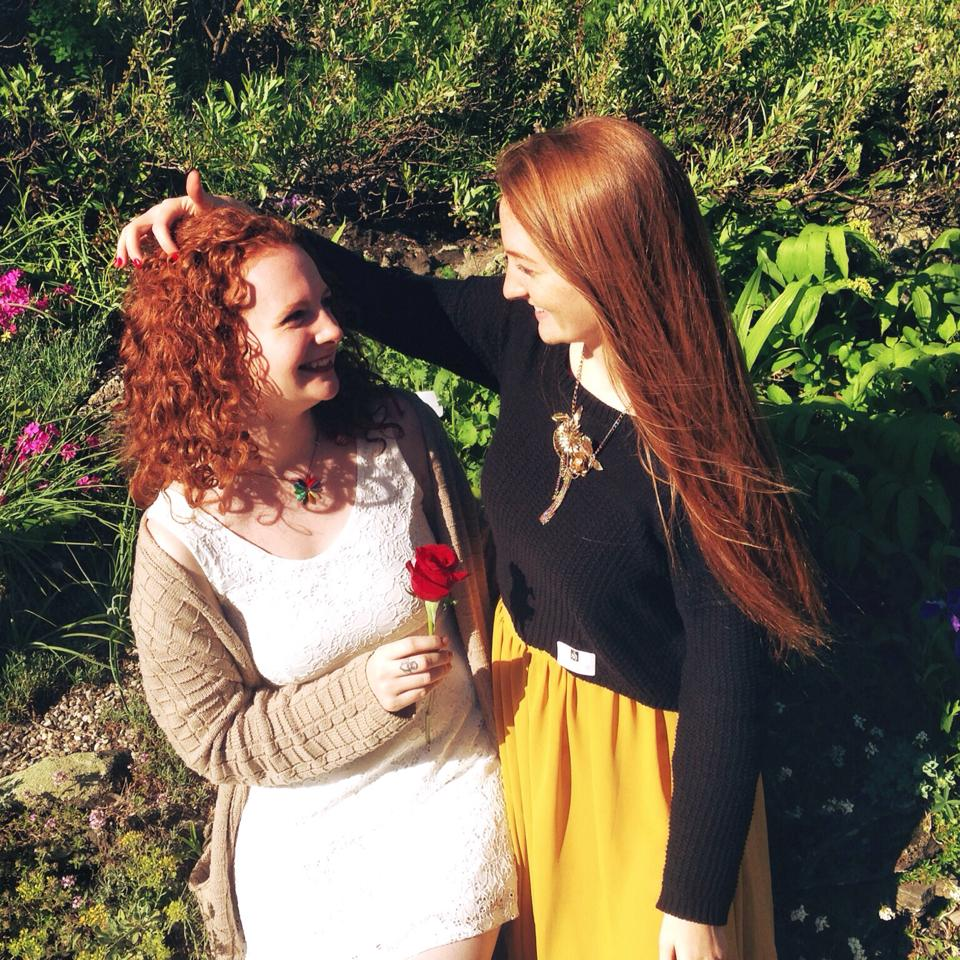 Two redhead sisters, one with straight hair and one with curly hair, sitting outside and smiling at each other.