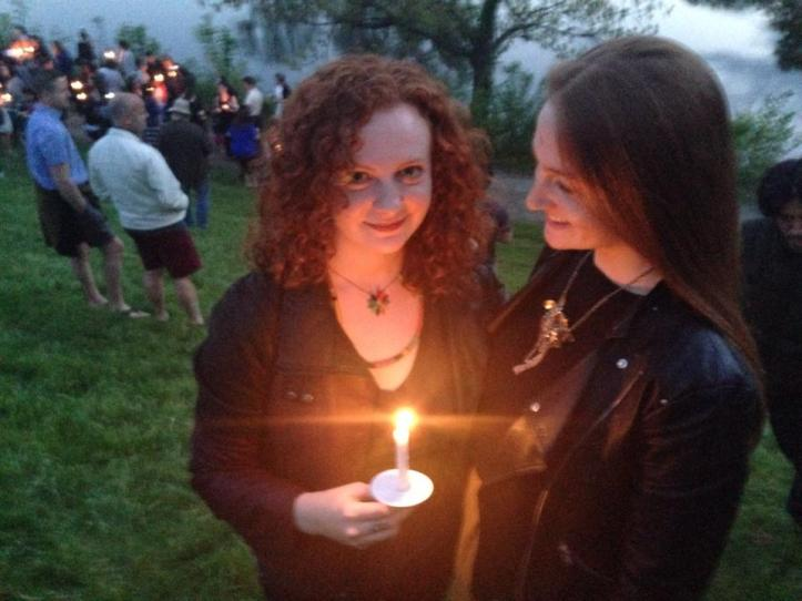 Two sisters, one holding a candle and the other looking at her, standing outside in the early evening light.