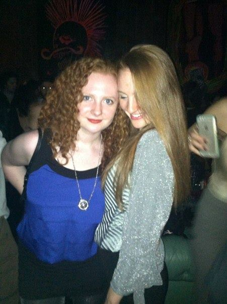 Two redhead sisters, one wearing blue, the other in gray, smiling on the dance floor of a club.