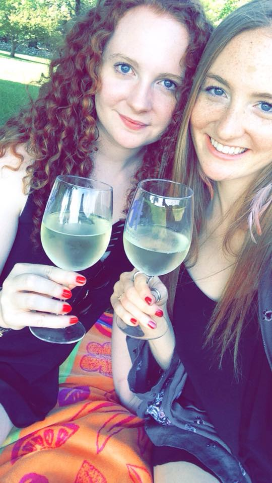 Two sisters smiling and clinking their glasses of white wine together as they sit outside.