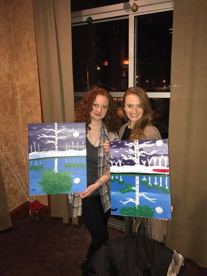 Two redhead sisters smiling and posing with paintings that they made.