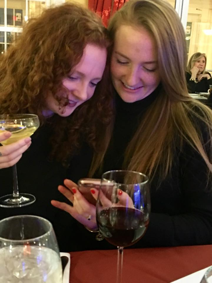 Two redhead sisters looking down at their phone and smiling while sipping on drinks at a restaurant.