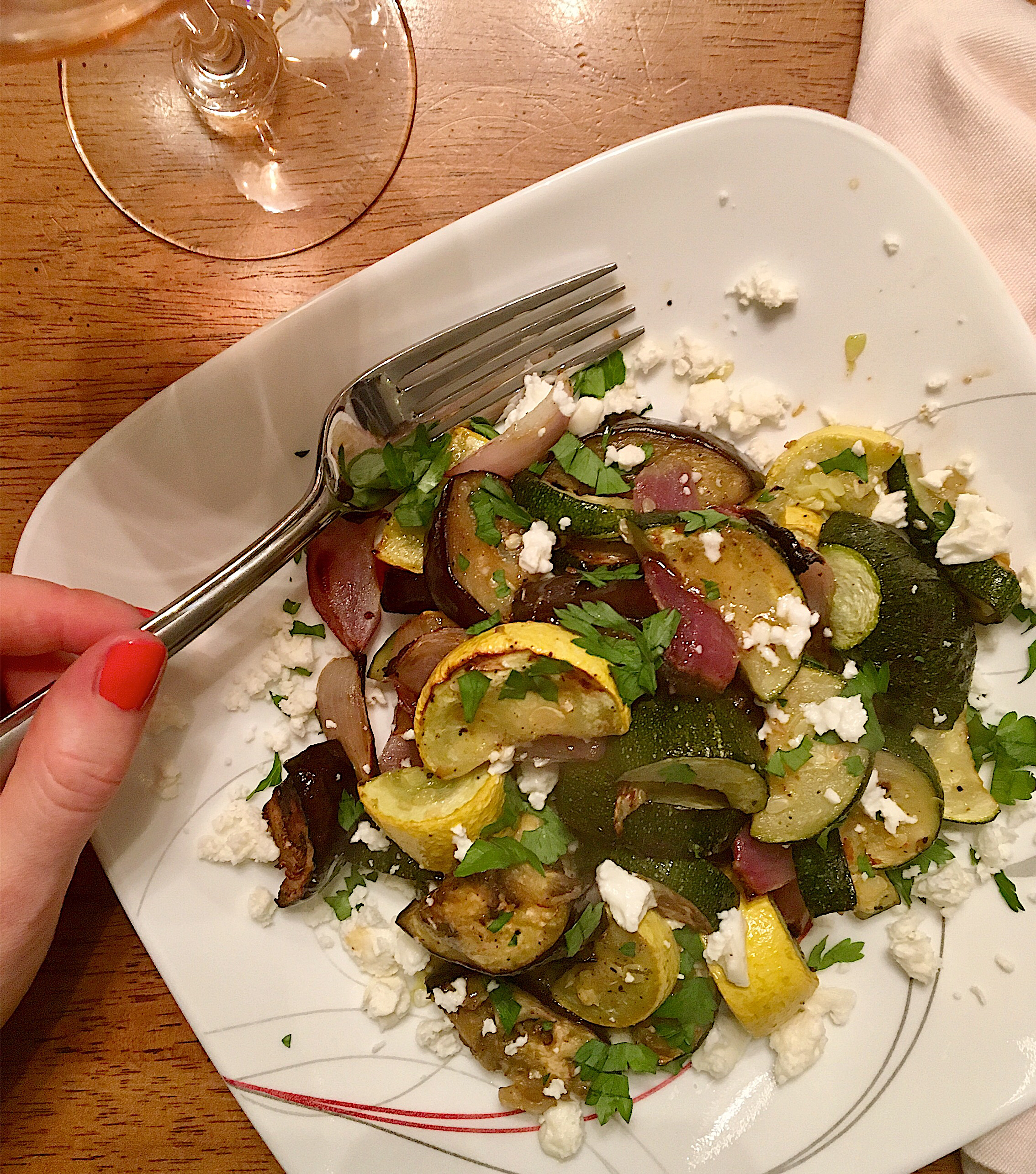 Roasted yellow squash, zucchini, eggplant, and red onion piled on a white plate, drizzled with red wine vinaigrette and sprinkled with feta cheese and parsley.